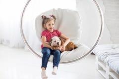 坐在与牛头犬小狗的一把垂悬的椅子的美丽的女孩 免版税图库摄影