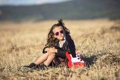 坐在与玩具吉他的领域的小石城女孩 免版税库存图片