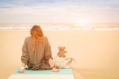 坐在与玩具熊的海滩的年轻单身妇女 免版税库存图片