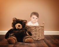 坐在与玩具熊的篮子的小婴孩 库存图片