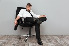 坐在与瓶的办公室椅子的愉快的被喝的商人 免版税库存图片