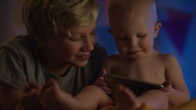 坐在与电话和微笑的坏和观看的动画片的可爱宝贝他的兄弟做公司 股票视频