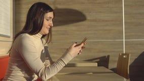 坐在与电话的咖啡馆的年轻深色的妇女 虚拟的通信 影视素材