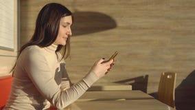 坐在与电话的咖啡馆的年轻深色的妇女 虚拟的通信 库存图片