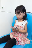 坐在与电话的MRT里面的亚裔中国小女孩 免版税库存照片