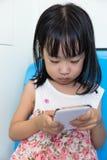 坐在与电话的MRT里面的亚裔中国小女孩 免版税图库摄影