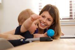 坐在与男婴的桌上的微笑的妇女 免版税库存图片