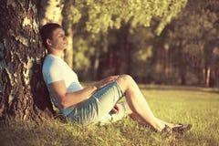 坐在与眼睛的一棵树下的松弛人结束了思考享受在外形的温暖的晚上日落 图库摄影