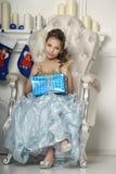 坐在与礼物的一把椅子的美丽的女孩 库存照片