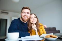 坐在与票据的桌上的微笑的夫妇 免版税库存照片