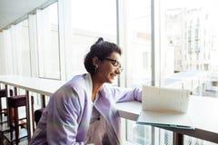 坐在与笔记本读书,佩带的玻璃,生活方式愉快的微笑的人民的咖啡馆的年轻逗人喜爱的行家女学生 免版税库存照片