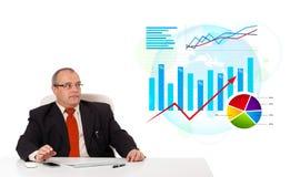 坐在与统计数据的服务台的生意人 免版税库存图片