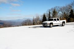 坐在与美丽的其他山天空和看法的一座积雪的山顶部的白色卡车在距离的 库存照片