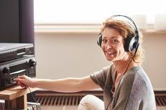 坐在与耳机的伴音系统旁边的老妇人 库存照片