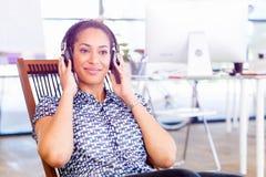 坐在与耳机的offfice的微笑的美国黑人的办公室工作者画象  免版税库存照片