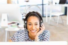 坐在与耳机的offfice的微笑的美国黑人的办公室工作者画象  图库摄影