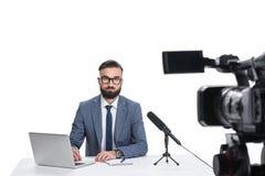 坐在与膝上型计算机、笔记薄和话筒的桌上和看照相机的男性新闻广播员, 库存照片