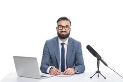 坐在与膝上型计算机、笔记薄和话筒的桌上的愉快的男性新闻广播员, 图库摄影