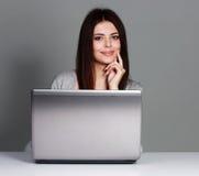 坐在与膝上型计算机估计的桌上的年轻偶然妇女 免版税库存照片