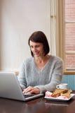 坐在与膝上型计算机和食物的咖啡馆的妇女 免版税库存图片