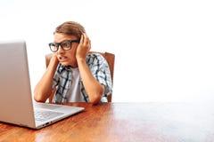 坐在与膝上型计算机的一张桌上的一个年轻人,被冲击由什么他看盖子他的耳朵听不到,青少年的惊奇的神色在lapto 库存图片
