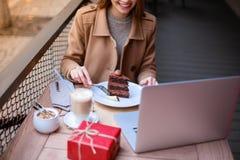坐在与膝上型计算机的咖啡馆和吃巧克力点心的愉快的女孩 户外 库存照片