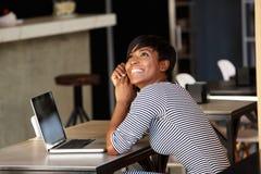 坐在与膝上型计算机的咖啡馆的快乐的少妇 库存照片