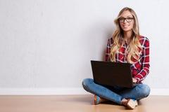 坐在与膝上型计算机的地板的年轻创造性的妇女 / 偶然b 免版税图库摄影