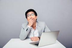 坐在与膝上型计算机的桌上的惊奇商人 免版税库存照片