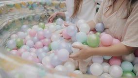 坐在与色的球的可膨胀的浴和荡桨他们的女孩对他的手 她庆祝 女孩的手的特写镜头 股票录像
