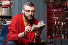 坐在与蜡烛的桌上和享受自修的有胡子的占卜者 免版税库存照片