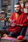 坐在与蜡烛的桌上和拿着预言的卡片的占卜者 图库摄影