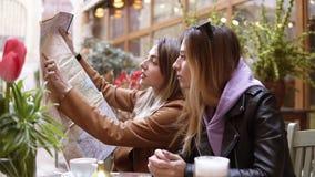 坐在与被伸出的地图的开放terrrace咖啡馆的两个美丽的白种人女孩 计划他们的旅行或进来 股票视频