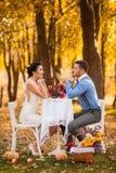 坐在与装饰的一张桌上的微笑的夫妇在秋天停放 愉快的新娘和新郎在森林里,户外 免版税库存照片
