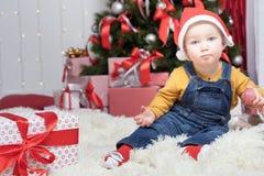坐在与许多礼物盒的圣诞树附近的滑稽的婴孩 免版税库存图片