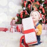坐在与许多礼物盒的圣诞树附近的滑稽的婴孩 库存照片