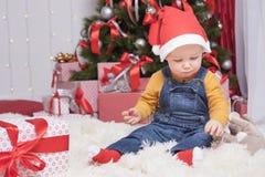 坐在与许多礼物盒的圣诞树附近的滑稽的婴孩 免版税库存照片