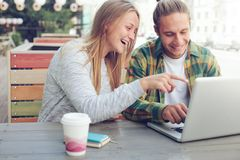 坐在与谈论膝上型计算机,快乐和微笑的夫妇的街道咖啡馆的男人和妇女计划 库存照片