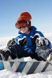 坐在与雪板的雪的新男孩 图库摄影