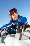 坐在与雪板的雪的新男孩 免版税库存照片