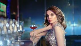 坐在与鸡尾酒的酒吧的时兴的性感的妇女中景画象在党期间 股票视频