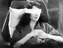 坐在与绷带的一把椅子的少妇在她的眼睛(所有人被描述不更长生存,并且庄园不存在 补助 免版税库存照片