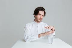 坐在与水玻璃的桌上的体贴的年轻人 免版税库存照片