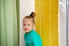 坐在与黄色水平的窗帘的窗口的美丽的女孩 库存照片
