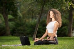 坐在与a的瑜伽位置的少妇 库存图片