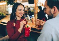 坐在与ac人的俱乐部的美丽的女孩 她在她的手上拿着一杯鸡尾酒 她看给人 免版税库存图片