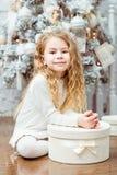 坐在与g的圣诞树下的可爱的白肤金发的小女孩 免版税库存图片