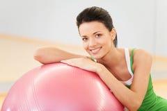 坐在与pilates球的健身房的妇女 免版税库存图片