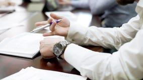 坐在业务会议和转动的笔的乏味雇员在他的手上 免版税库存图片