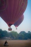坐在两个热空气气球前面的亚裔人 免版税图库摄影